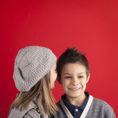 Couple of kids whispering on red background with copyspace. Valentines — Zdjęcie stockowe