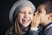 Couple of kids whispering on black background — Stock Photo