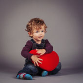 Little kid with red heart. Studio shot — Stock Photo