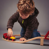 Little kid playing with train construction. Studio shot — Stock Photo