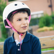 Six year old kid outdoor wearing helmet portrait. - Stock Photo