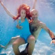Father and daughter having fun underwater in swimming pool. — Stock Photo