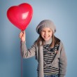 Young smiling girl with red heart balloon on blue background. — Stock Photo #19999069