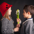 Boy offering flower on black background. Valentines day concept. — Stock Photo