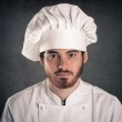 Portrait of a young cook man with pan wearing uniform over grunge background — Stock Photo
