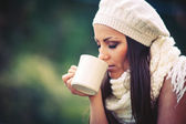 Young woman drinking from a cup outdoors in the nature. — Stock Photo