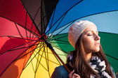 Young woman with multicolored umbrella. — Stock Photo