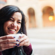 Smiling woman drinking coffee in a cafe outdoors. Shallow depth of field. — Foto Stock