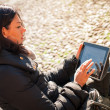 Woman using tablet to surf the web outdoors. — Stock Photo #21629795