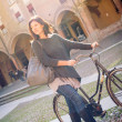 Woman walking with bicycle in Saint Stephen square, Bologna, Italy. — Stock Photo #21629807