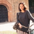 Woman walking with bicycle in Saint Stephen square, Bologna, Italy. - Stock Photo