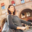 Woman walking with bicycle in Saint Stephen square, Bologna, Italy. — Stock Photo #21629831