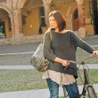 Woman walking with bicycle in Saint Stephen square, Bologna, Italy. — Stock Photo #21629835