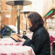 Stock Photo: Womusing tablet outdoors sit in bar. Shallow depth of field.