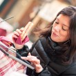 Smiling woman using tablet outdoors while having lunch. Shallow depth of field. — Stock Photo