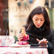 Woman using tablet outdoors sit in a bar. Shallow depth of field. — Stock Photo #21629883