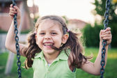 Little smiling girl swinging close up portrait. — Stock Photo