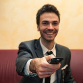 Happy business man pointing remote control. Selective focus image. — Stock Photo