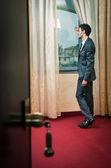 Einsamer mann am fenster im hotelzimmer. — Stockfoto