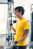 Young girl exercising with dumbbells in the gym. — Stock Photo