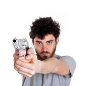 Young killer pointing a gun over white background. — Stock Photo