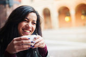 Smiling woman drinking coffee in a cafe outdoors. Shallow depth of field. — Stock Photo