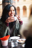 Young woman drinking coffee in a cafe outdoors. Shallow depth of field. — Stok fotoğraf