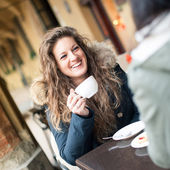 Young woman drinking coffee with friend in a cafe outdoors. Shallow depth of field. — Stock Photo