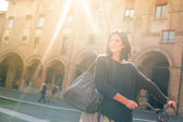 Woman walking with bicycle in Saint Stephen square, Bologna, Italy. Back light. — Stock Photo
