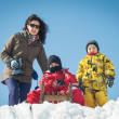 Happy family having fun on the snow with sled. — Stock Photo