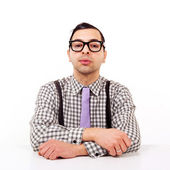 Funny portrait of young nerd with eyeglasses at the desk isolated on white background. — Stock Photo
