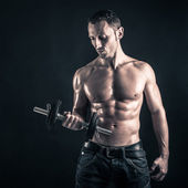 Confident young man shirtless portrait training with dumb-bell against black background. — Stock Photo