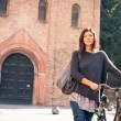 Woman portrait with bicycle in Saint Stephen square, Bologna, Italy. — Stock Photo #23084436