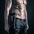 Confident young man shirtless portrait with machine gun against black background. — Stock Photo