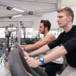 Young men training in the gym with bike.  — Stock Photo