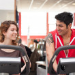 Young couple training in the gym with bike while talking together. — Stock Photo