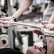 Young man lifting the barbell in the gym with instructor. Focus on hand. — Stock Photo