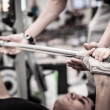Young man lifting the barbell in the gym with instructor. Focus on hand. - Stock Photo