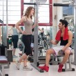 Young friends talking at the gym while training. - Stock Photo