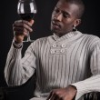 Confident portrait of young african man tasting glass of red wine. — Stock Photo