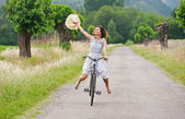 Pretty young woman riding bike in a country road. — Стоковое фото