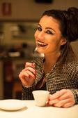 Elegante donna sorridente che bere il caffè in un bar. tempo di notte. — Foto Stock