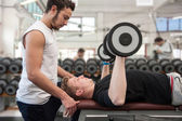 Man and his personal trainer exercising with dumbbells at the Gym. — Stock Photo