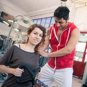 žena cvičení s její osobní trenér v posilovně. — Stock fotografie