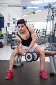 Young man exercising with dumbbells in a gym. — Stock Photo