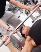 Young man lifting the barbell in the gym with instructor. — Stock Photo