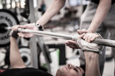 Young man lifting the barbell in the gym with instructor. Focus on hand. — Foto de Stock