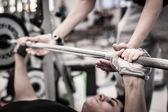 Joven levantar la barra en el gimnasio con instructor. centrarse en mano. — Foto de Stock
