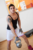 Young man training in the gym with heavy ball. — Stock Photo