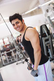 Young smiling man training in the gym. — Stock Photo